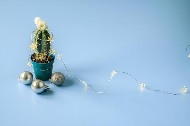 Cactus versierd met kerstverlichting en ornamenten op blauw