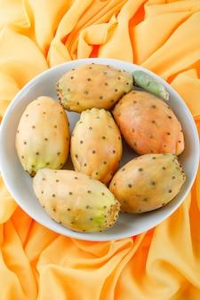 Cactusvruchten in een witte plaat op geel textieloppervlak