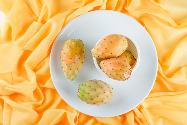 Cactusvruchten in kom en plaat op een geel textieloppervlak