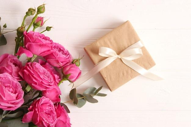 Cadeau en bloemen op een gekleurde achtergrond. vakantie, geef een cadeau, gefeliciteerd. valentijnsdag, moederdag, internationale vrouwendag. hoge kwaliteit foto