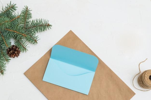 Cadeau-envelop gemaakt van kraftpapier op een achtergrond van dennentakken brief en handgemaakte envelop voor kerstmis.