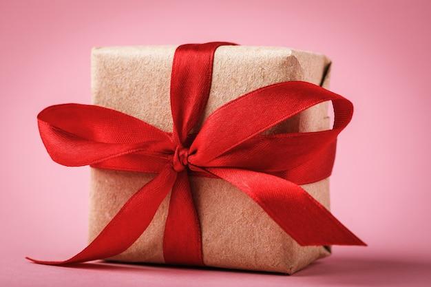 Cadeau gebonden met rood lint op roze achtergrond close-up