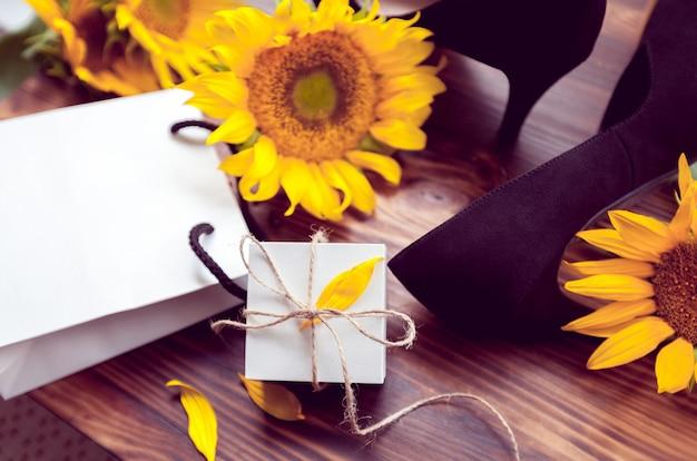 Cadeau, gele zonnebloemen en schoenen met zwarte hakken