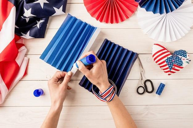 Cadeau-idee, decor 4 juli, usa independence day. stap voor stap zelfstudie diy ambacht. kleurrijke papieren waaiers maken, stap 4 - papier lijmen, aan elkaar plakken. platliggend bovenaanzicht