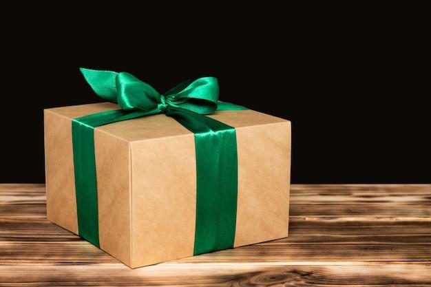 Cadeau in ambachtelijk papier met een groen lint op een donkere rustieke verbrande houten achtergrond. ruimte kopiëren.