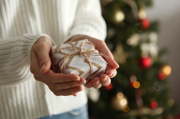 Cadeau in handen voor kerstmis of nieuwjaar op een achtergrond van een versierd interieur