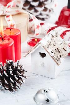 Cadeau in kraft doos met rode sterren lint, aangestoken kaarsen en decoraties