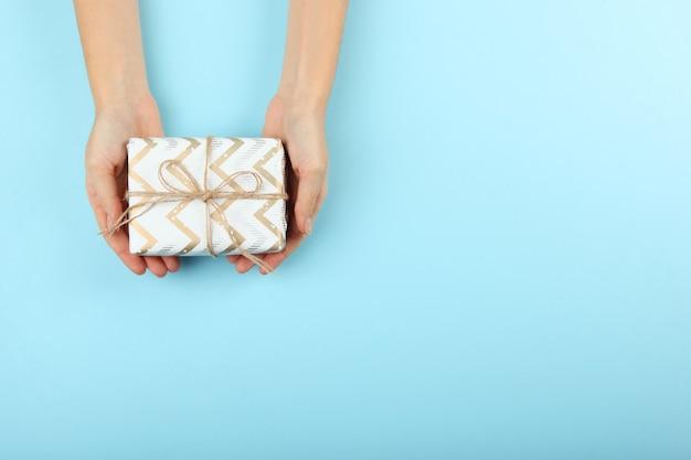 Cadeau in vrouwelijke handen op een gekleurde achtergrond bovenaanzicht