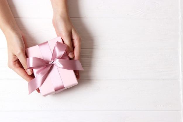 Cadeau in vrouwelijke handen op een gekleurde achtergrond met confetti bovenaanzicht