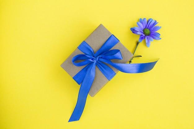Cadeau met blauwe strik en een blauwe bloem in het midden van de gele tafel. bovenaanzicht. kopieer ruimte.