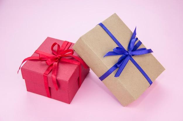 Cadeau met een blauw en rood lint op een roze achtergrond. geschenkverpakking. doos met plakband.