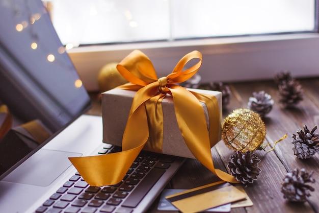 Cadeau met een gouden lint en een laptop en bankkaart op een houten tafel kerst online winkelen