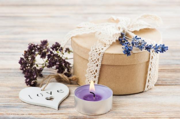 Cadeau met kanten strik, lavendel en verlichte kaars