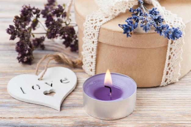 Cadeau met kanten strik, lavendel, verlichte kaars