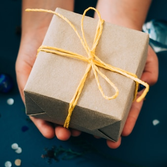 Cadeau verpakt in knutselpapier en vastgebonden met geel touw. handen met een geschenkdoos. vakantie feest en dankbaarheid expressie concept.