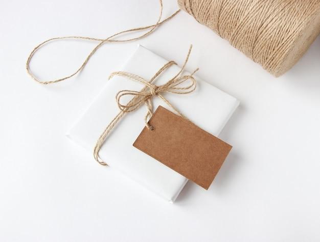 Cadeau verpakt in wit papier en omwikkeld met touw op een witte achtergrond met een label voor kopieerruimte