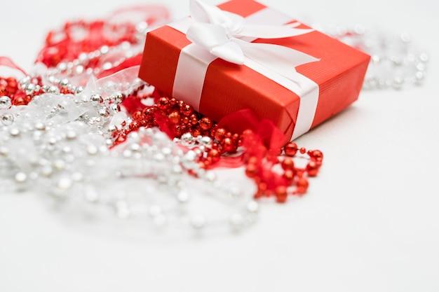 Cadeau voor een vrouw in een versierde rode geschenkdoos op een witte muur. mooie beloning voor een geliefd concept