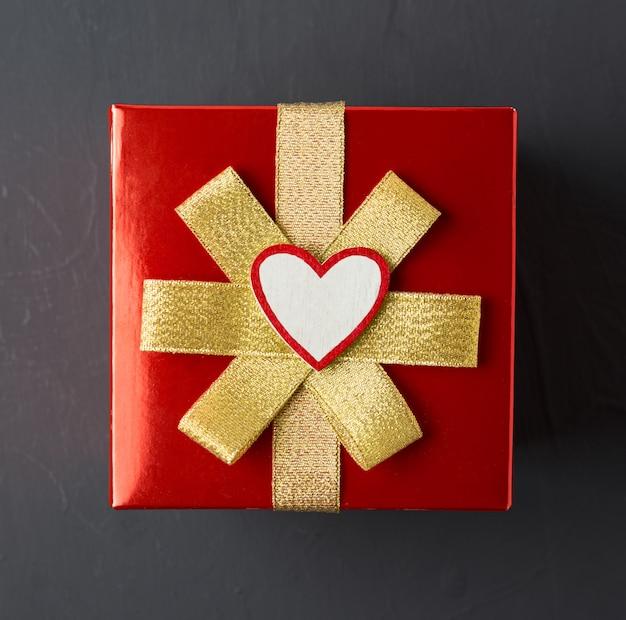 Cadeau voor valentijnsdag, verpakt in rood inpakpapier met goud