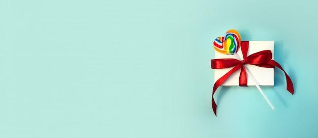 Cadeau voor valentijnsdag. witte geschenkdoos met rood lint en kleur lollipop op lichtblauw