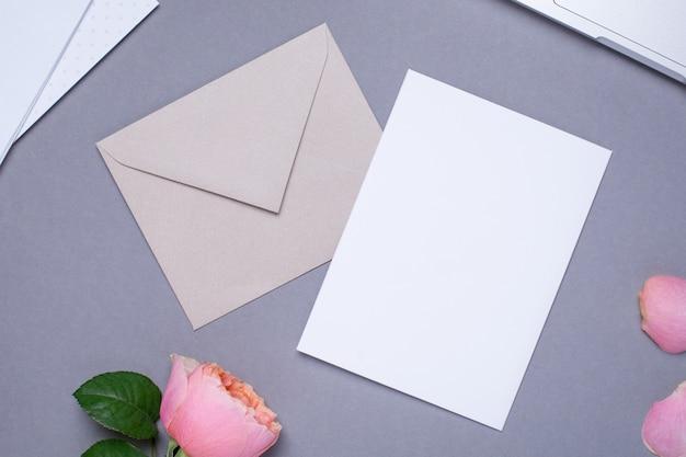 Cadeaubon en envelop met roze roos op grijs