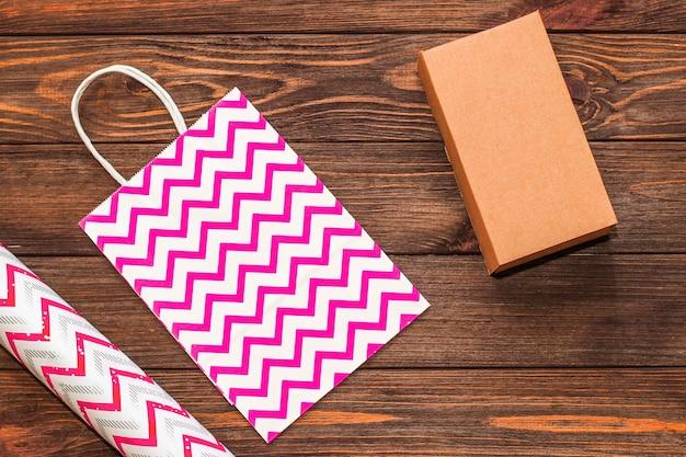 Cadeaupapier en roze tas en ambachtelijke verpakking op houten ondergrond.