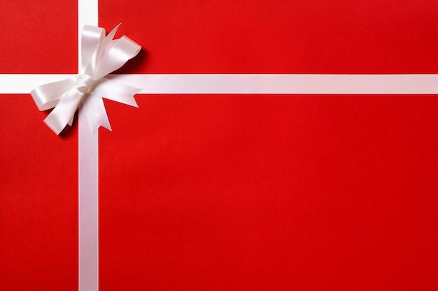 Cadeaupapier witte strik rood papier achtergrond
