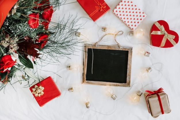 Cadeaus en lichte guirlande rond schoolbord
