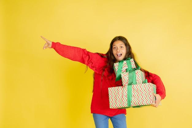 Cadeaus geven en krijgen tijdens de kerstvakantie. tienermeisje die pret hebben die op gele studio wordt geïsoleerd