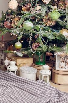 Cadeaus liggen op een geruite deken onder de kerstboom