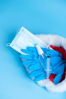 Cadeauset voor kerst en oud en nieuw 2021. een hygiënische set van een medisch masker, handschoenen, een ontsmettingsmiddel en een spuit met een vaccin en een coronaviruschip in een kerstmanhoed. vaccinatie 2021.