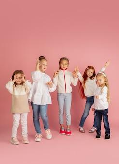 Cadeautjes geven en krijgen tijdens kerstvakantie. groep gelukkige glimlachende kinderen die pret hebben, vieren geïsoleerd op roze studioachtergrond. nieuwjaar 2021 ontmoeting, jeugd, geluk, emoties.