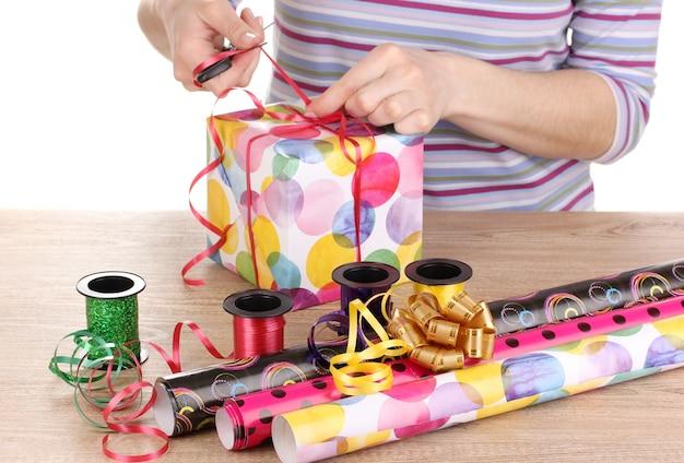 Cadeautjes inpakken omringd door papier, lint en strikken