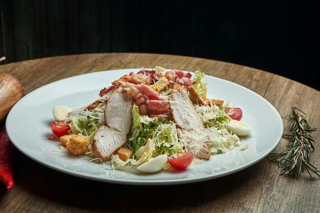 Caesar salade met croutons, parmezaanse kaas, spek, kip, ei in zwarte plaat op houten oppervlak. restaurant serveren. close-up met kopie ruimte. detailopname