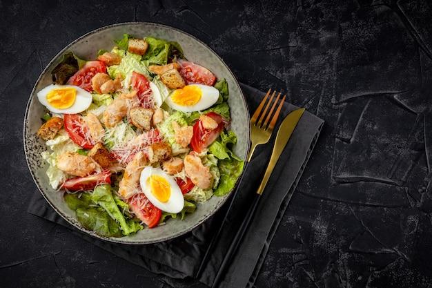 Caesar salade met kip op een zwarte achtergrond bovenaanzicht.