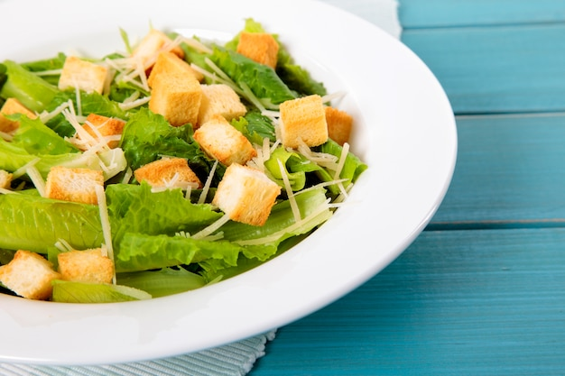 Caesar salade op blauwe picknick tafel