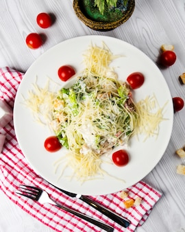 Caesarsalade met cherrytomaatjes en gehakte parmezaanse kaas.