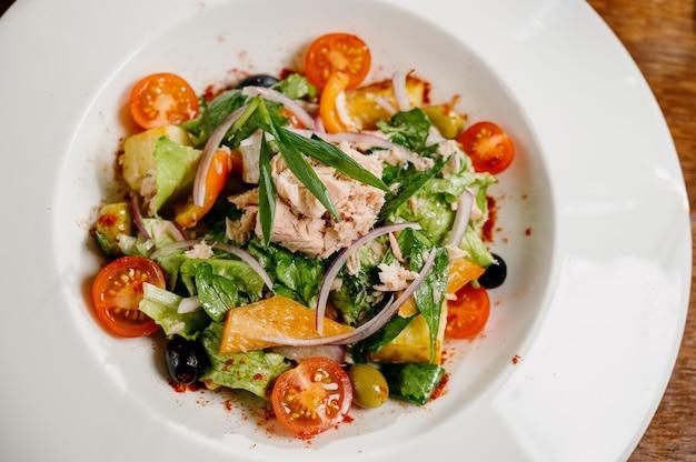 Caesarsalade met croutons, kwarteleitjes, kerstomaatjes en gegrilde kip in houten tafel