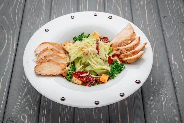 Caesarsalade met croutons, kwartelseieren, cherrytomaatjes en gegrilde kip op houten