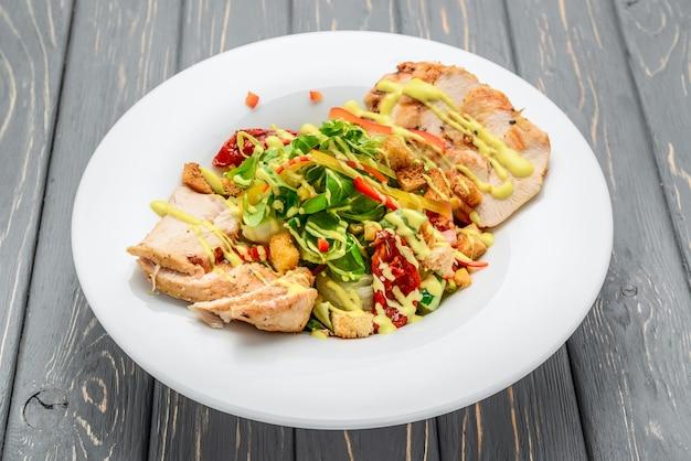 Caesarsalade met croutons, kwartelseieren, cherrytomaten en gegrilde kip op een houten tafel