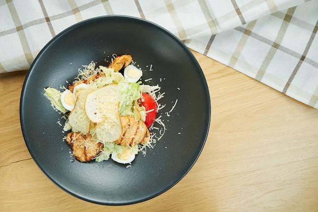 Caesarsalade met croutons, parmezaan, kip, ei in een zwarte stijlvolle kom. restaurant serveren. selectieve aandacht, houten tafel