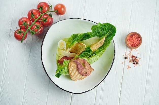 Caesarsalade met croutons, parmezaanse kaas, bacon, kip, ei in witte kom op witte achtergrond. restaurant serveren. close-up met kopie ruimte.