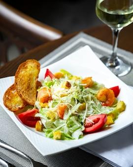 Caesarsalade met garnalen en glas wijn