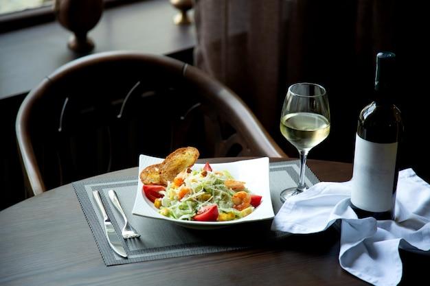Caesarsalade met garnalen en glas witte wijn