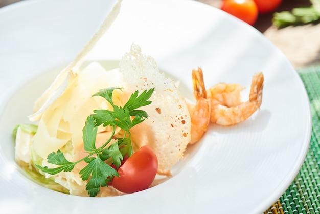 Caesarsalade met garnalen op een witte plaat worden gediend die