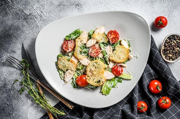 Caesarsalade met gegrilde kip, croutons, kwarteleitjes en kerstomaatjes. bovenaanzicht