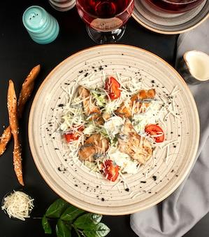 Caesarsalade met gegrilde kip, tomaten, parmezaanse sla, soepstengels en een glas compote