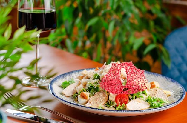 Caesarsalade met gegrilde kipfilet, romaine sla, eieren en croutons geserveerd met rode wijn. kopieer ruimte