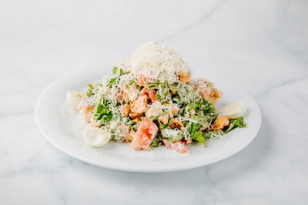 Caesarsalade met gemengde ingrediënten en gehakte kaas op de bovenkant op witte achtergrond.