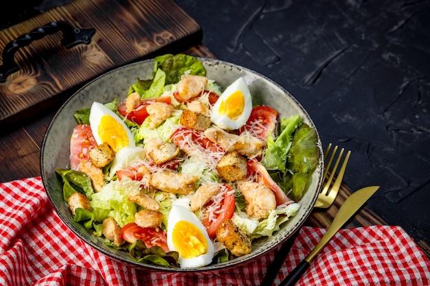 Caesarsalade met kip en eieren op een plaatclose-up.