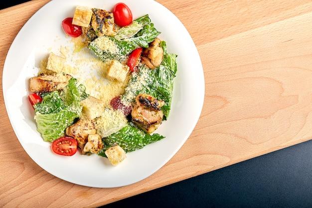 Caesarsalade met kip op houten lijst